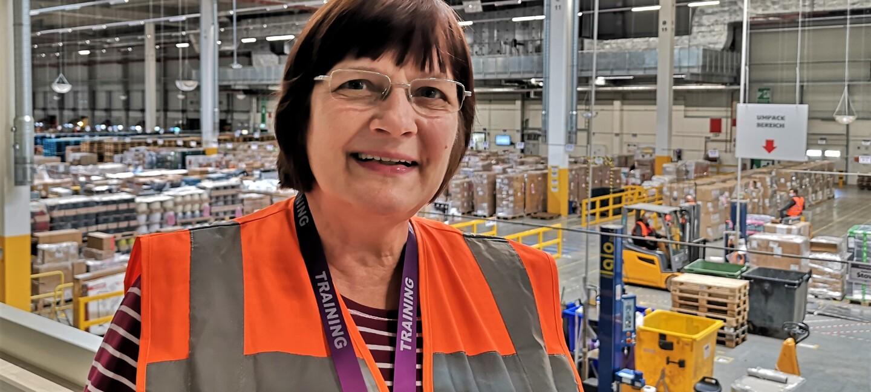 Eine Frau mit Brille und braunen Haaren, sie trägt eine orangene Sicherheitsweste. Im Hintergrund sieht man die Logistikhalle.
