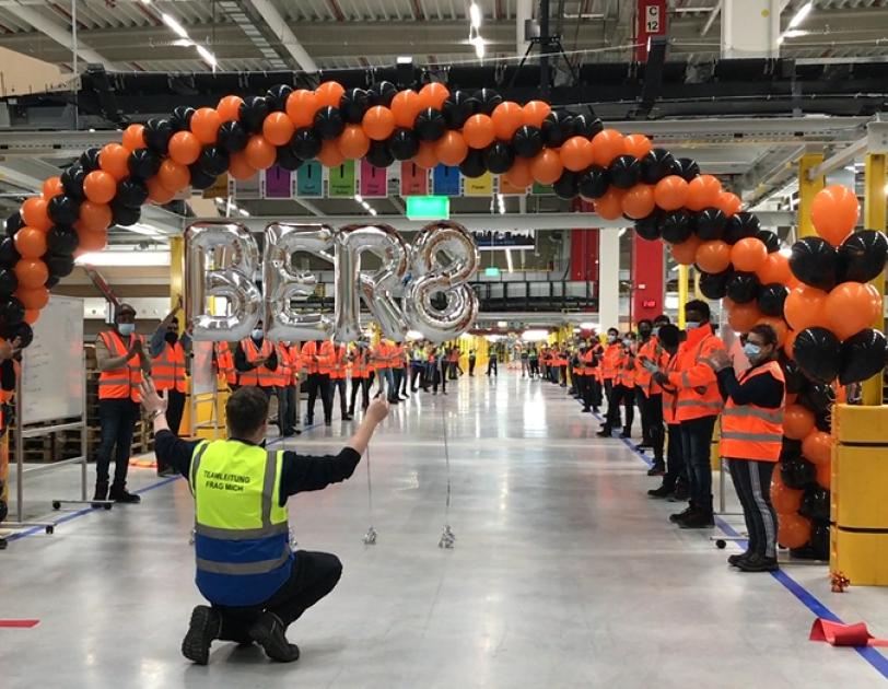 Mehrer Mitarbeiter mit Masken in einem Logistikzentrum: Alle klatschen, 2 Mitarbeiter halten einen Bogen mit schwarzen und orangenen Luftballons in die Höhe.