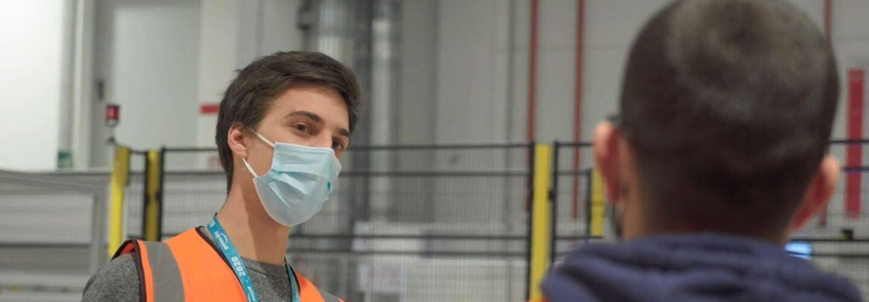 Dipendente Amazon in un magazzino che chiacchiera con un suo collega, girato di spalle. Il dipendente indossa una mascherina chirurgica e un giubbino catarinfrangente, è un uomo con i capelli scuri e corti.