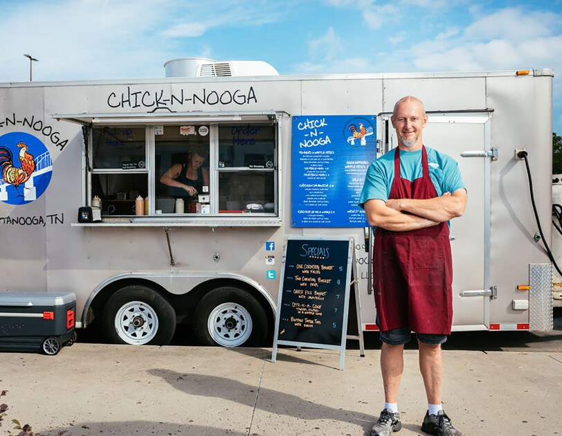 A man wearing a maroon apron stands with his arms crossed, in front of a  silver CHICK-N-NOOGA food truck. A sign displays the specials in neon orange text on a black background.