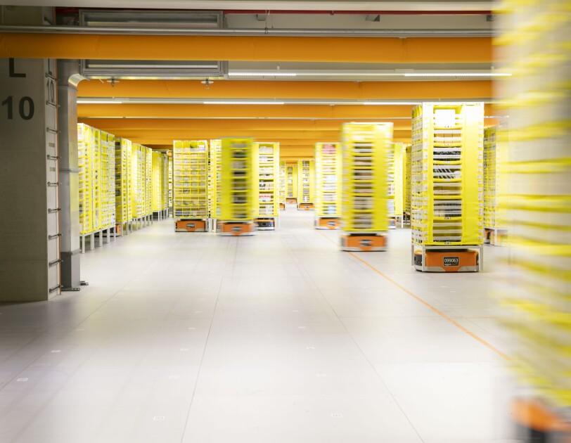Schmale gelbe Regale werden von den Transportrobotern durch das Logistikzentrum transportiert.