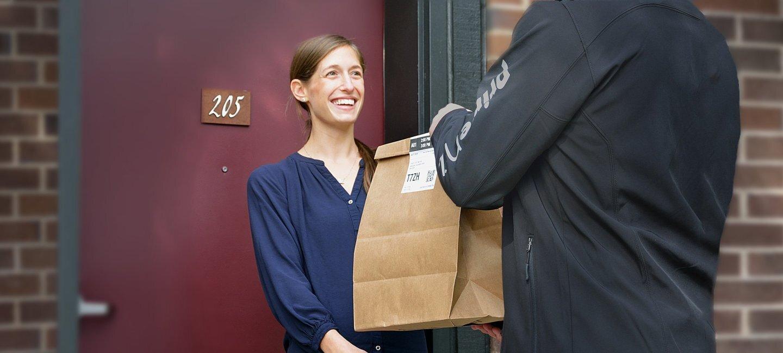 Repartidor de Prime Now con un chaqueta negra entrega una bolsa de papel de Amazon a una señora con una camisa azul que se encuentra en la puerta de su casa.
