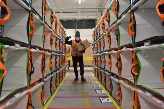 Un rullo corridoio in un magazzino Amazon. Al centro un operatore di magazzino con un pacco in mano.