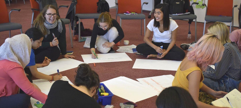 Junge Menschen mit verschiedenen Nationalitäten sitzen im Kreis auf den Boden und malen Plakate.