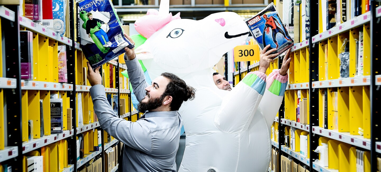 Owen from MorphCostumes pictured picking a comic book from a shelf to the left and Alin from Amazon, who is wearing a white inflatable unicorn morphsuit, picking a comic book from a shelf on the right