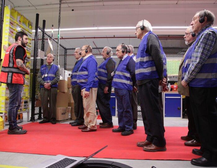 Nueve ingenieros jubilados durante la visita a un centro logístico. Todos ellos visten con un chaleco y escuchan atentamente las explicaciones del ingeniero que lleva un chaleco rojo.
