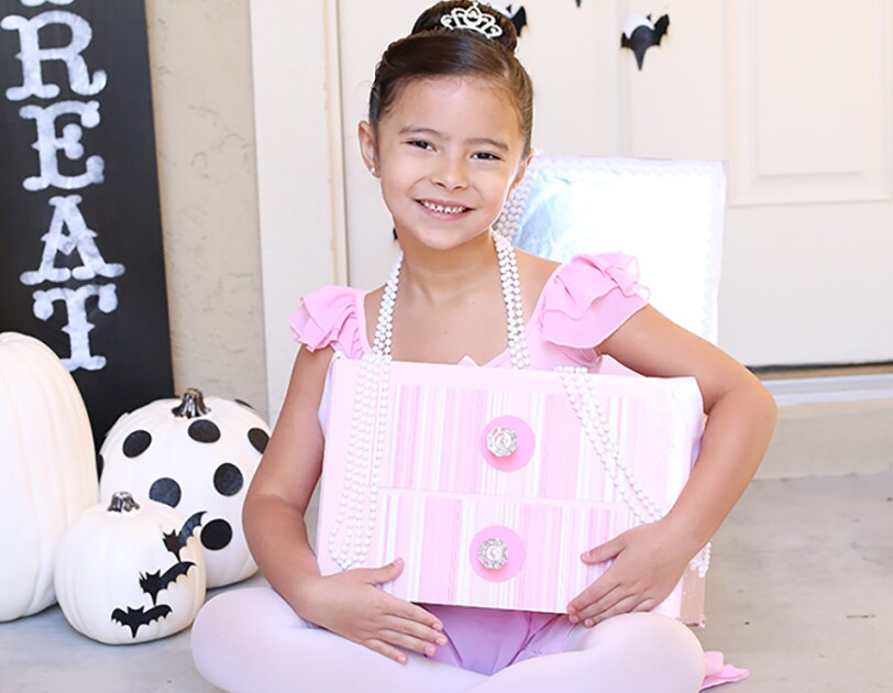 "A little girl in a costume made from an Amazon box. The box is crafted to look like a jewelry box. The girl is wearing ballet slippers, tights, a leotard, pearl necklaces and a tiara. The costume is a ""jewelry box ballerina"""