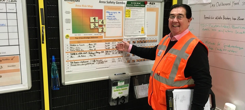 Ein lächelnder Mann mit orangener Sicherheitsweste, Brille und dunklen Haaren steht vor einer Sicherheitstafel im Logistikzentrum. In der Hand hält er ein Clipboard, das mehrere Blätter hält.