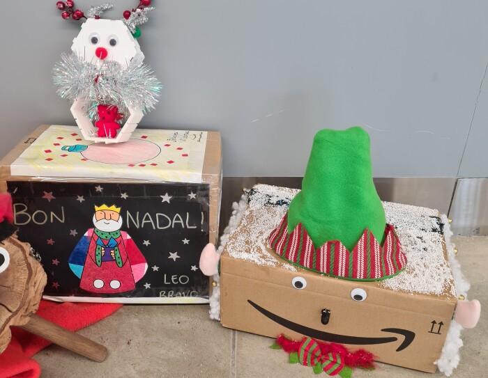 Adorno navideño de BCN1.  Un tió (tronco navideño típico catalán) y una caja con una felicitación navideña y otra caja que representa un elfo.
