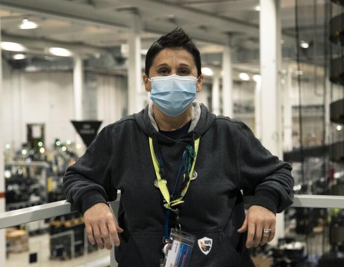 Una donna con i capelli corti indossa una mascherina chirurgica sul volto e poggia i gomiti su una balaustra alle sue spalle. Sullo sfondo di vede l'interno di un magazzino Amazon. La foto è scattata a mezzo busto.