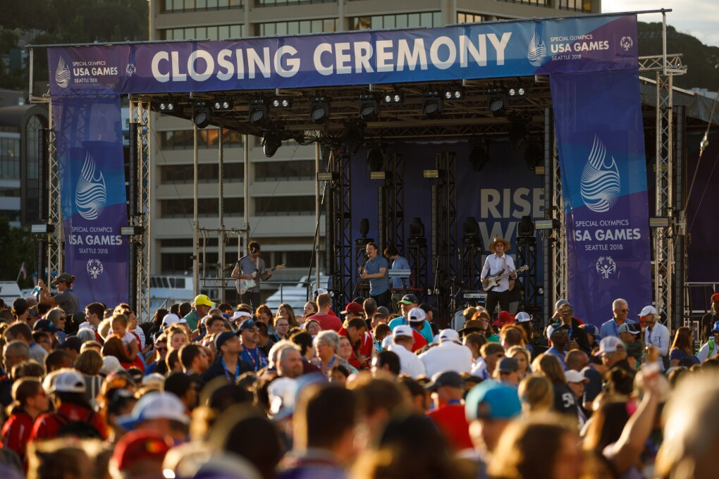 "The 2018 Special Olympics USA Games closing ceremony stage. Seattle band ""Hey Marseilles"" performs (in the photo, a singer, bass player, keyboardist and electric guitarist), with a crowd of individuals in front of the stage."