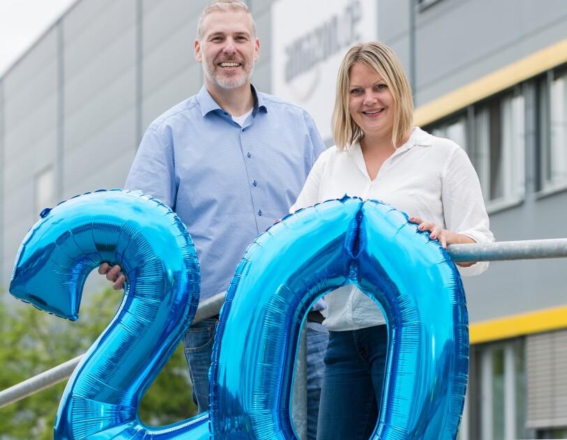 Ein Mann in blauem Hemd und Jeans und eine blonde Frau in weißer Bluse und Jeans stehen lächelnd vor einem Logistikzentrum. An der Fassade ist das Amazon.de Logo erkennbar. Beide halten blaue, aufgeblasene Zifffern - 2 und 0 - vor sich.