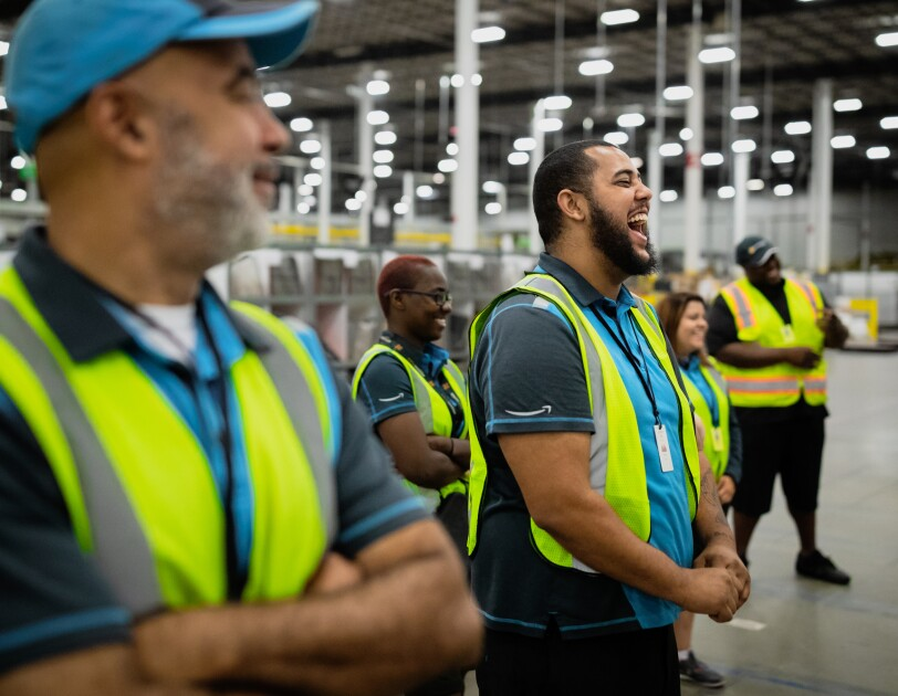 People wearing safety vests stand in a warehouse. A man near the center of the image is enjoying a laugh.