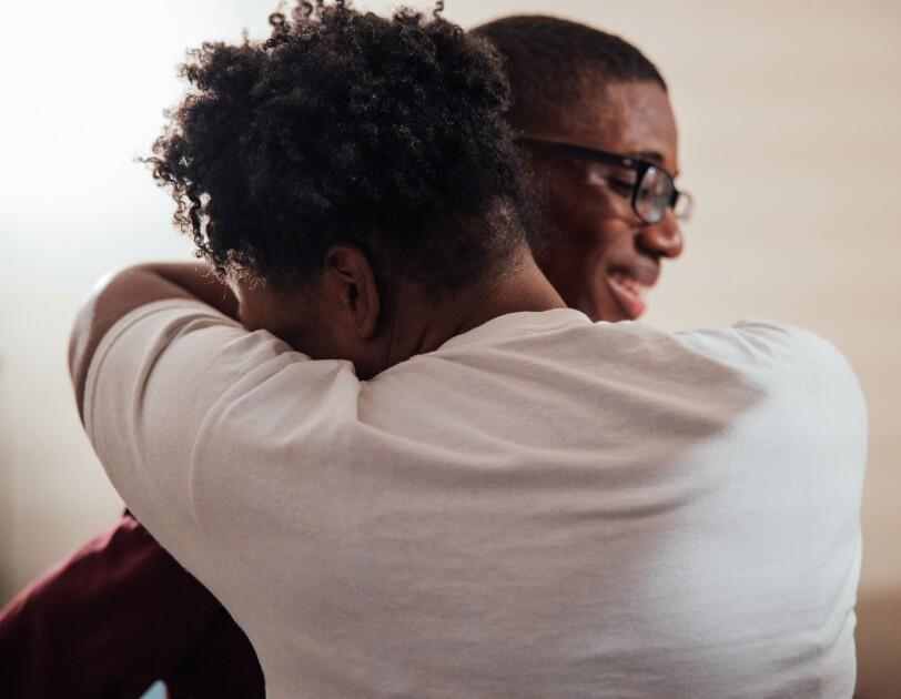 A woman hugs a teenage boy.