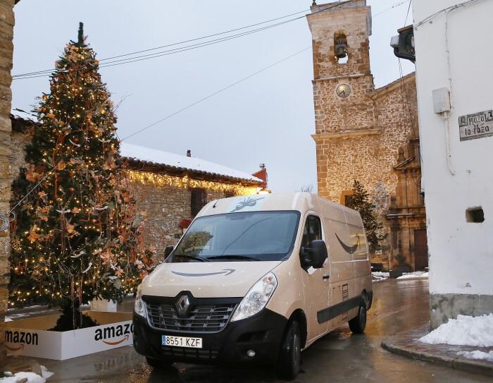 Plaza de la iglesia de Valdelinares. Hay un árbol de Navidad decorado. Una furgoneta de Amazon decorada como si fuera un apquetes y de fondo una iglesia de piedra. En el suelo hay nieve.