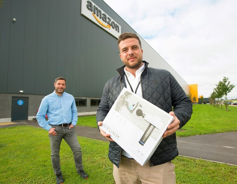 Business owner stood in front of Amazon fulfilment centre holding product in a box