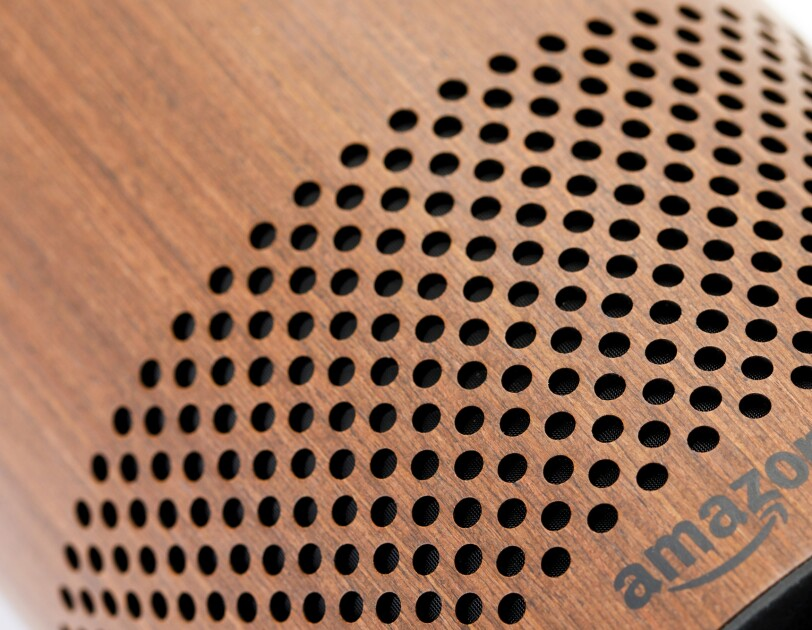 The speaker of a wood Amazon Echo tower.