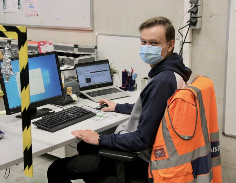 Mitarbeiter mit Maske am Bildschirm im Logistikzentrum