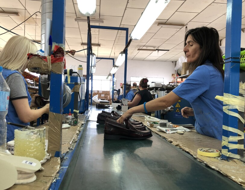 Shoe production  done by female employees of Castellanisimos, a Spanish shoe company. Employees wearing blue shirts lining the classic type male shoes on the production band.