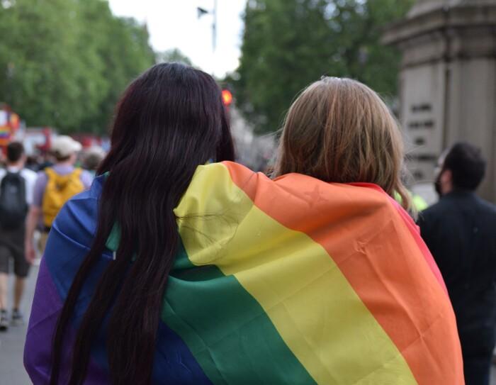 Es una foto con dos personas de pelo largo, moreno y rubio, de espaldas y tapados con una bandera del orgullo con el arcoiris. De fondo y desenfocados se ven personas andado en lo que parece un desfile. Se aprecia un autobús tojo de dos pisos con la bandera del orgullo. Por el autobús de dos pisos pensamos que es Londres.