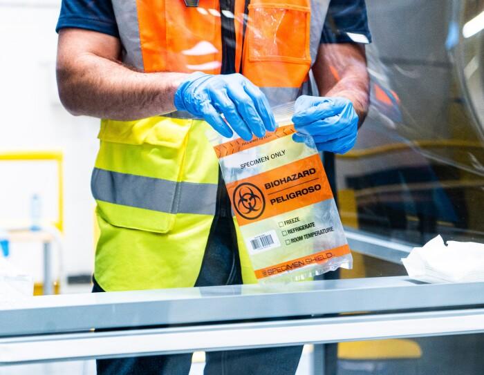 Nacho Carbonell realizándose una PCR en el centro logístco de El Prat de Llobregat. Nacho Carbonell colocando la muestra para que se analice. Con unos guantes de color azul, cierra una bolsa con la muestra para analizarla. El plano es de medio cuerpo con las manos. Va con una camiseta negra de manga corta y un chaleco naranja y amarillo.