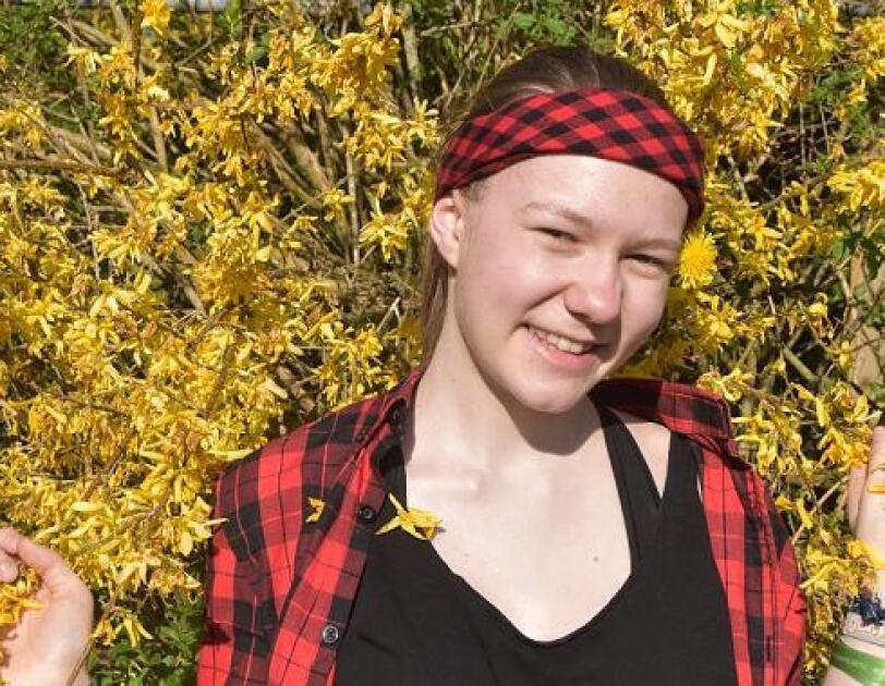 Ein Mädchen mit rotem Haarband steht vor einer Blumenhecke und schaut in die Kamera. Sie lächelt und sieht fröhlich aus.