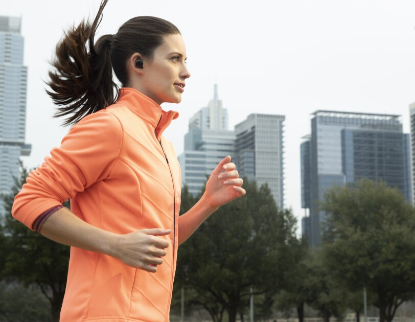 A woman running on a street wearing Echo Buds