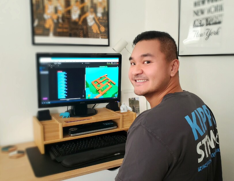 A man sitting at a desk with a computer on it turns around and smiles toward the camera.