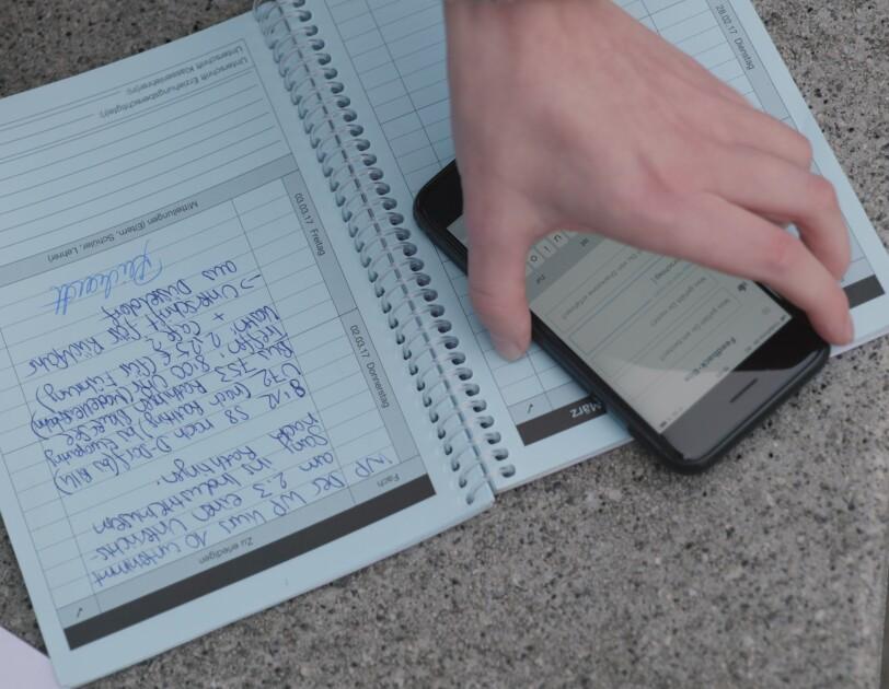 Auf einem Tisch liegen ein Hausaufgabenheft und ein Handy.