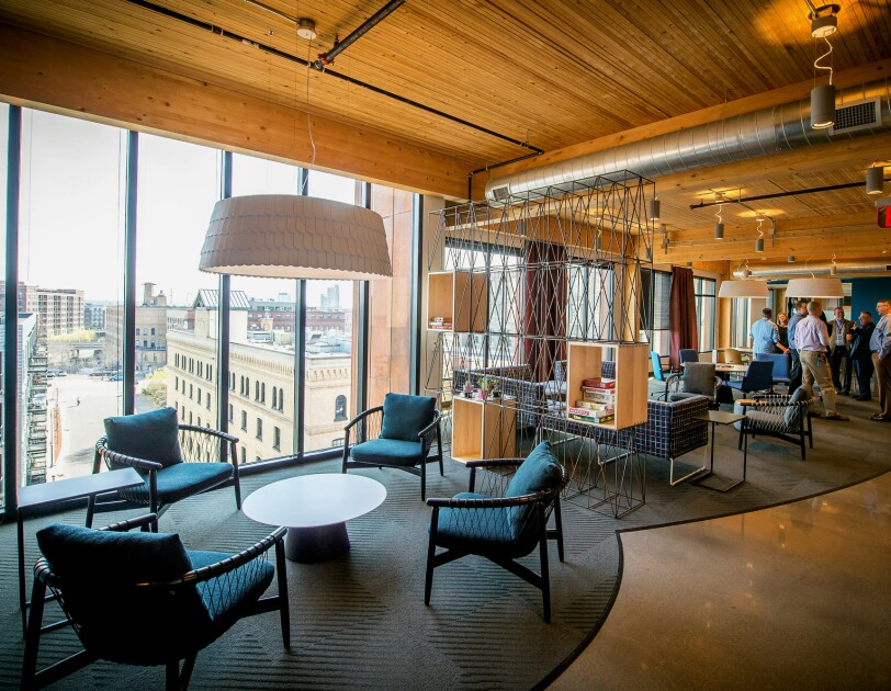 The view inside Amazon's Minneapolis tech hub - a wall of windows looks over nearby buildings, warm wood ceilings and exposed ventilation system are seen above casual co-working spaces. In the background, Amazonians gather.