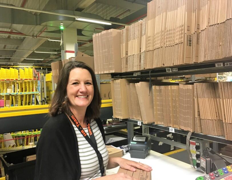 Eine Frau mit halblangen dunkelbraunen Haaren sitzt an einer Packstation, hinter ihr sind gefaltete Kartonagen zu sehen. Sie lächelt in die Kamera