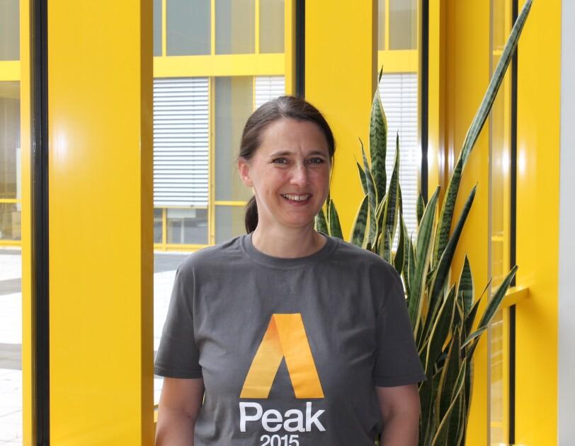 """Eine Frau mit braunem Pferdeschwand und einem grauen T-Shirt mit Aufschrift """"Peak 2015"""" steht vor einer gelb eingefassten Glastüre."""