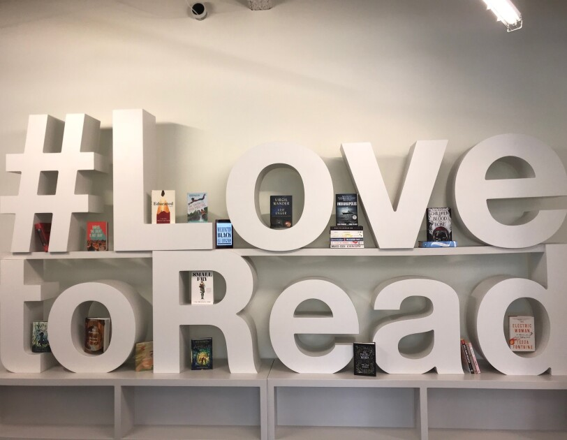 Large letters on a bookshelf spell out #LovetoRead. Between letters are some of the top books of the year.