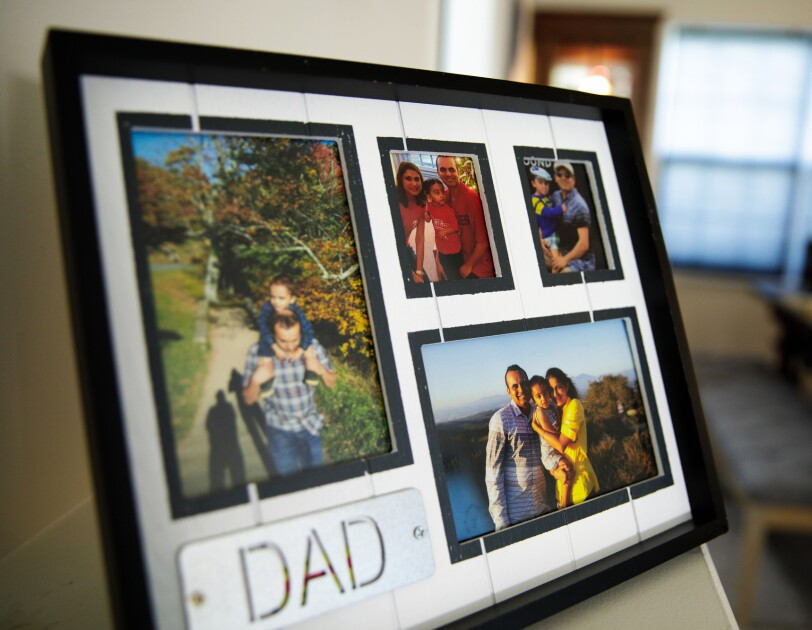"A picture frame with four separate family photos. The word ""dad"" is in all-capital letters in the bottom left of the frame."