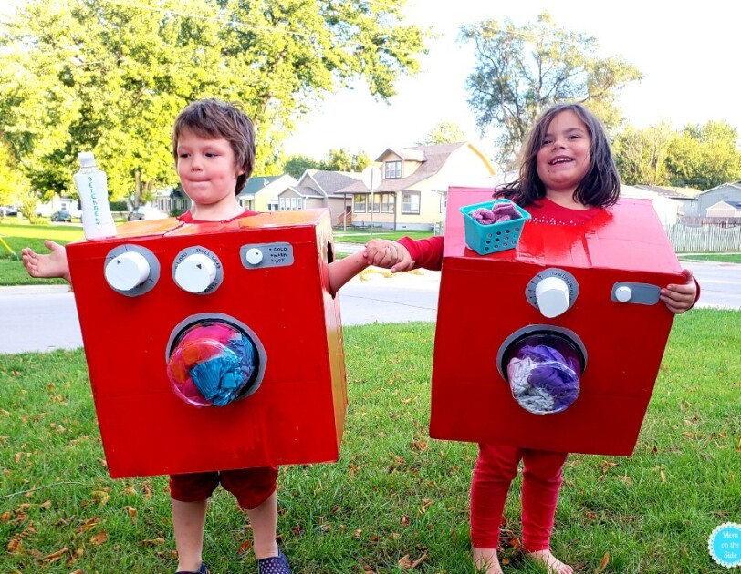 "Two young children stand side-by-side, each wearing a red box. Both boxes have a clear ""window"" on the front that shows clothing, which look as though they're tumbling in the laundry. The child on the left has a bottle that says ""detergent"" on the top of the box, and two knobs. The child on the right has a small basket that looks like a laundry basket with socks, and one knob."