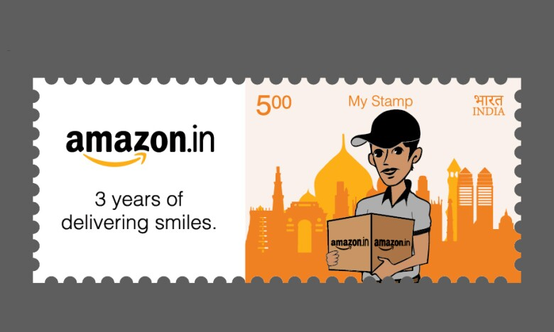 """Image of a stamp worth 5 Indian Rupees. The design shows a delivery person holding a box marked """"amazon.in"""" and standing in front of a skyline in the distance. The stamp also bears the words """"amazon.in"""" and """"3 years of delivering smiles."""""""