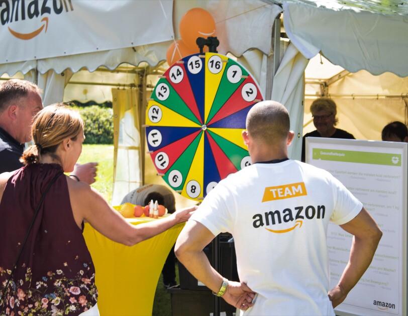"""Ein Amazon Mitarbeiter steht vor einem bunten Glücksrad. Er ist von hinten zu sehen. Auf dem Shirt ist """"Team Amazon"""" zu lesen."""