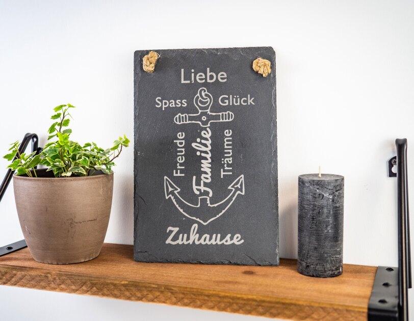 """Auf einem Holzregal steht eine Schieferplatte mit einem weißen Anker und Stichworten """"Familie, Zuhause, Glück, Spass"""""""