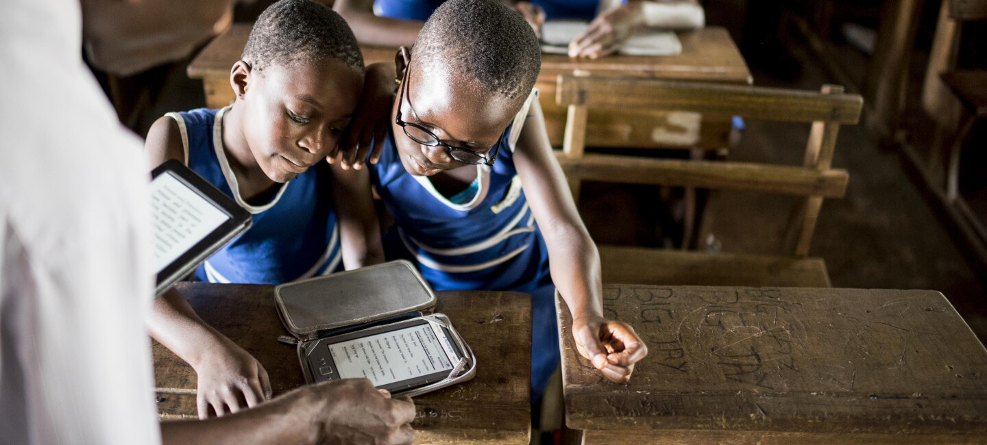 A group of school children in blue school uniforms huddle around a Kindle Worldreader at a school in Africa.