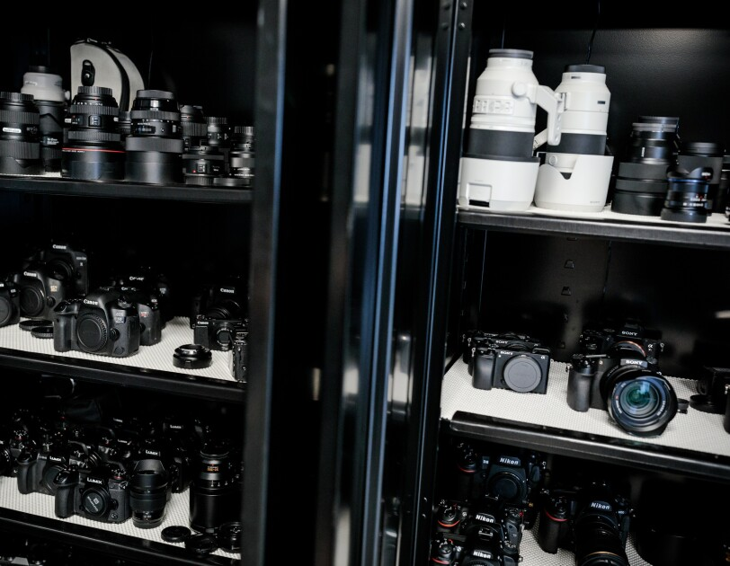 A closed metal cabinet with glass doors holds dozens of cameras and lenses.