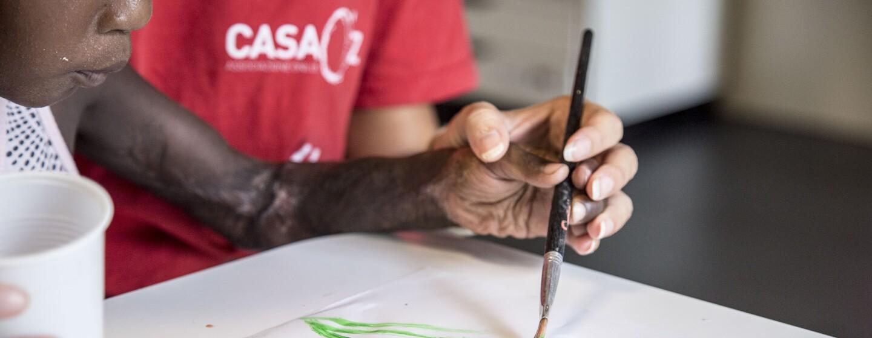 Un bimbo che dipinge su un foglio di carta a CasaOz