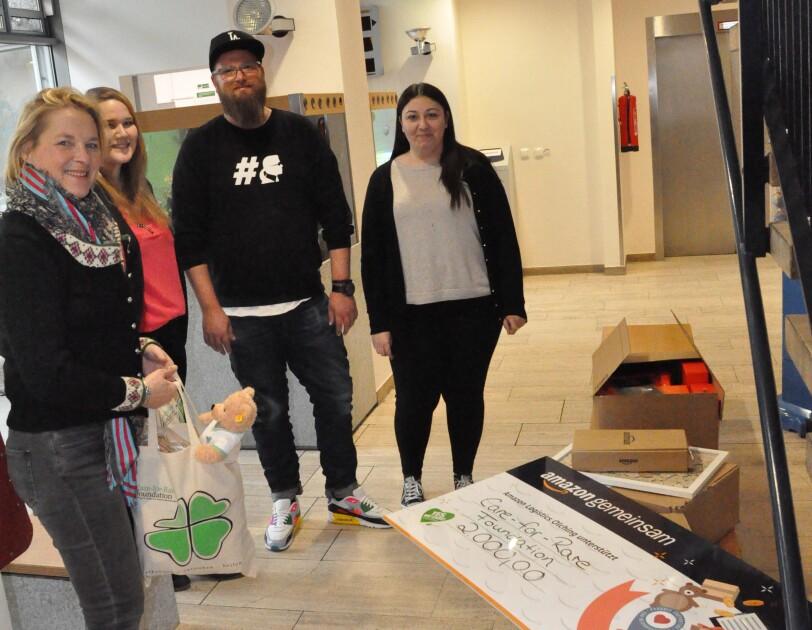 Eine Gruppe von Menschen hat sich um einen Spendenscheck versammelt