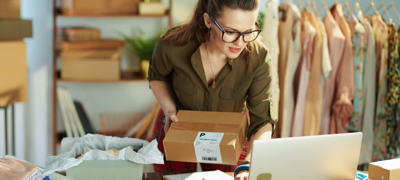 Eine Frau mit Brille steht vor einem Laptop und hat ein Paket in der Hand.
