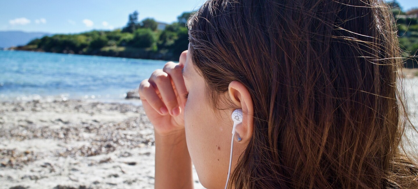 A girl listening wearing headphones and sitting on a beach