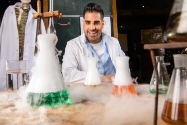 Dr. Ranj Magic Breakfast in front of a table filled with test tubes and science experiments.