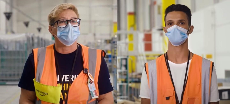 Un uomo e due donna ripresi a mezzo busto all'interno di un magazzino Amazon. Tutti e tre indossano una mascherina chirurgica sul volto e un giubbino catarinfrangente da lavoro.
