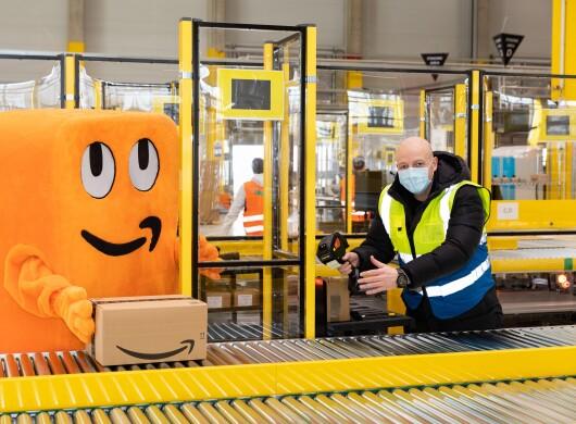 Das orangene Amazon Maskottchen Peccy am Rollband mit dem Standortleiter.