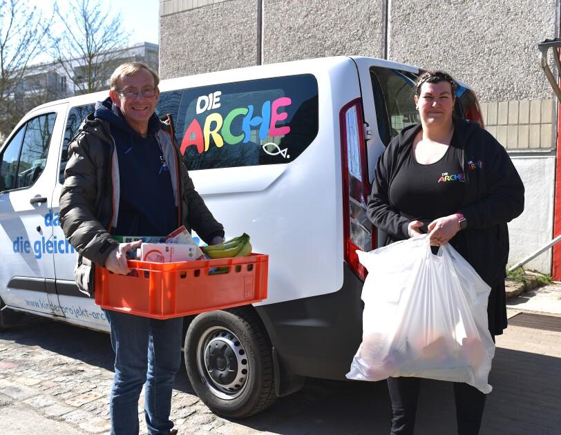 """2 Mitarbeiter der Arche mit Lebensmitteln vor einem Lieferwagen mit Aufdruch """"Die Arche""""."""