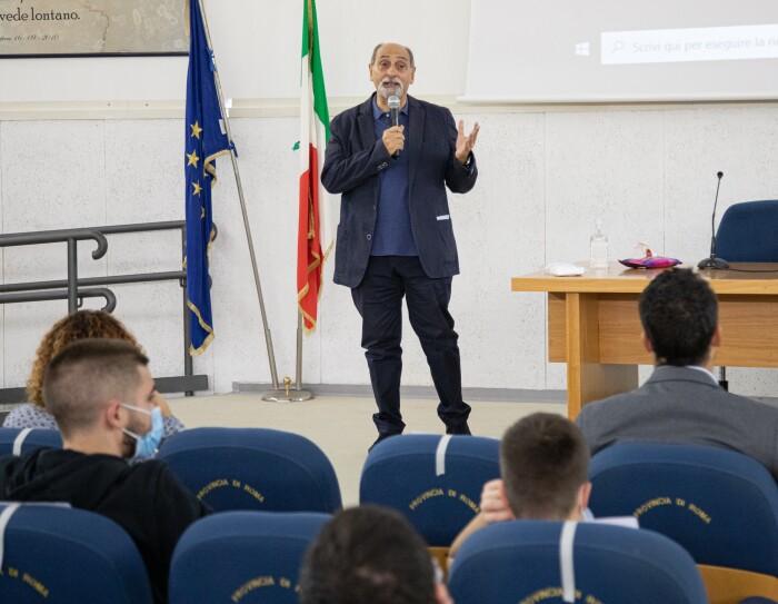 Foto di Umberto Guidoni mentre parla con gli studenti. Guidoni tiene un microfono nella mano destra, ha la barba bianca. Alle sue spalle vediamo una bandiera dell'Europa e una dell'Italia.
