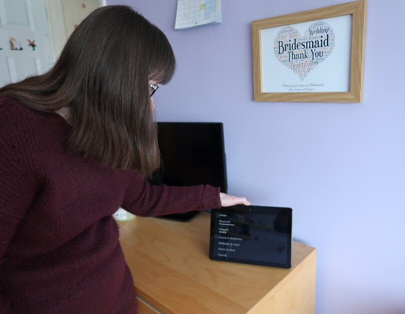 Holly Tuke's stood next to device in own home